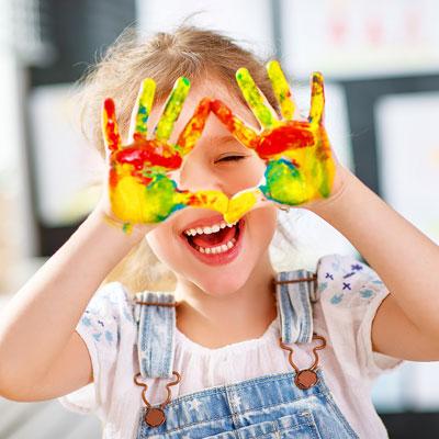 Kind lachend mit farbigen Händen
